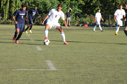 Captain Vinny Silva dribbling the ball away from  Lawrence.