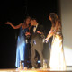 Former Malden High School students Cristina Valente and Elyse Valente escort Alex Gentile on stage.